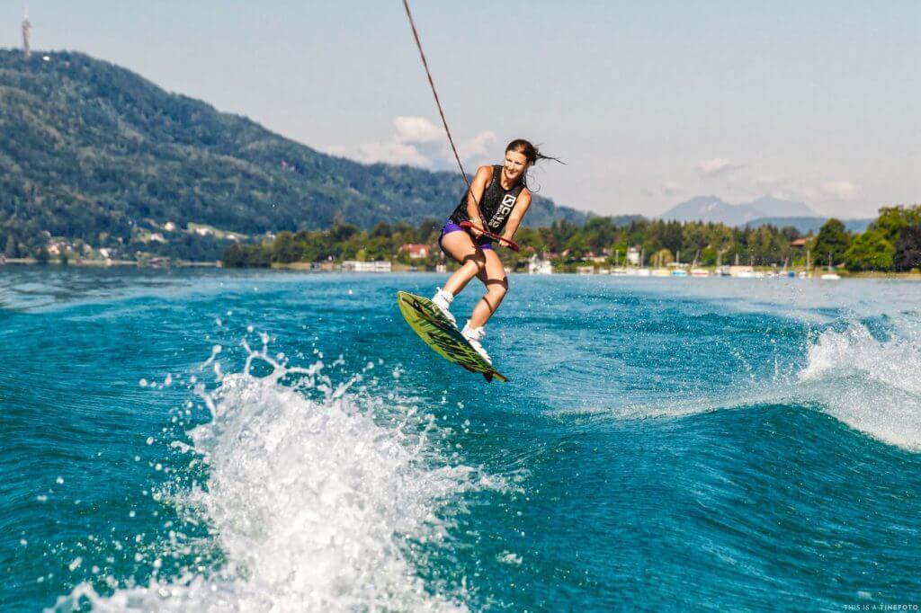 Wakeboarderin springt über die Heckwelle des Bootes