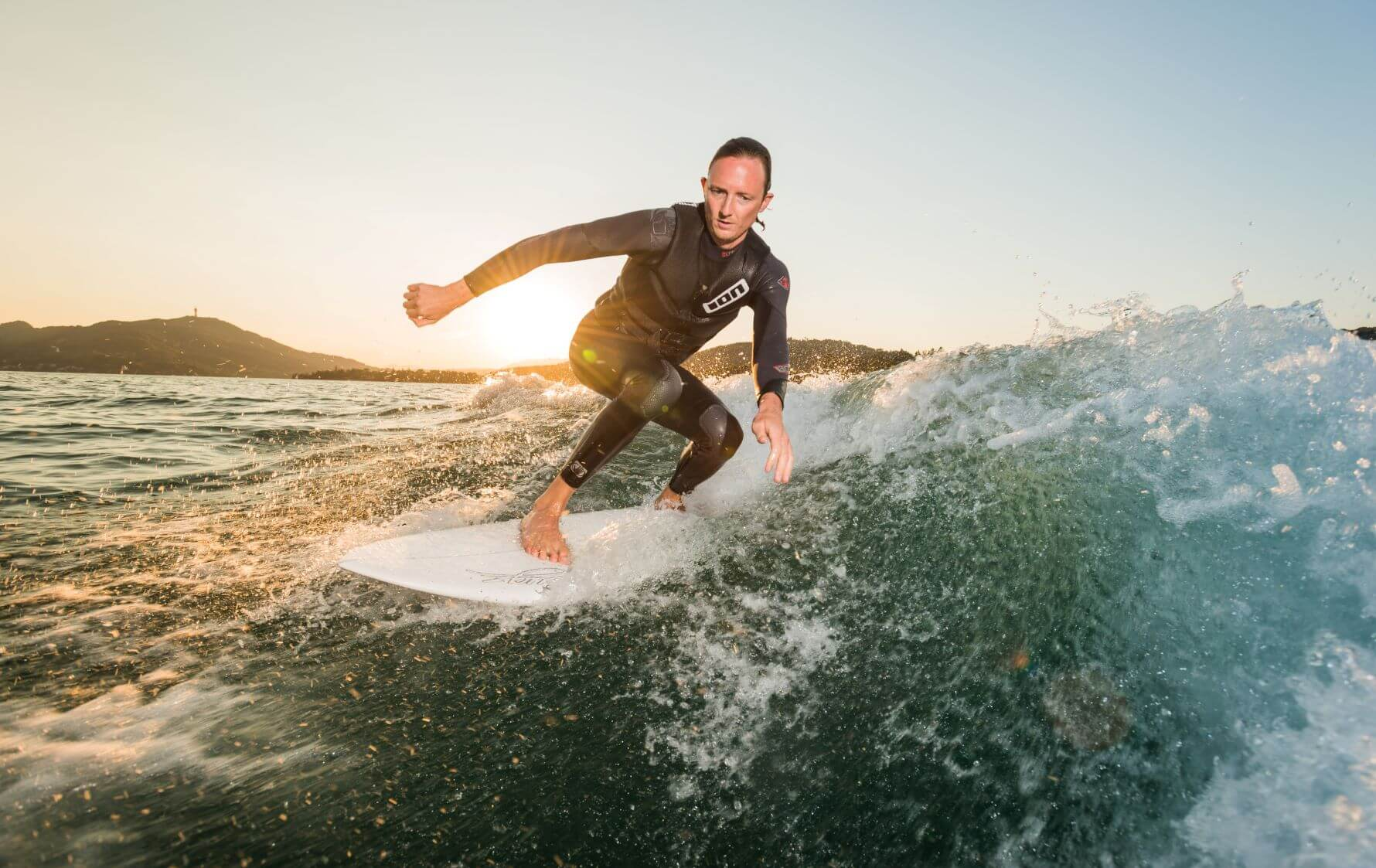 Mann surft im Sonnenuntergang auf einer stehenden Welle am Wörthersee.